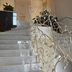 Scala in marmo Bianco di Carrara e Pietra Grey e ringhiera di design in ferro battuto: Scale in stile  di Canalmarmi e Graniti snc