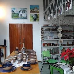 Vista da loja e do guarda-corpo do mezanino (ateliê): Casas pré-fabricadas  por Hérmanes Abreu Arquitetura Ltda