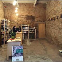 interior del local pared de piedra original: Oficinas y Tiendas de estilo  de projectelab