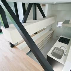 リビングから半層下がったキッチン: 石川淳建築設計事務所が手掛けたシステムキッチンです。