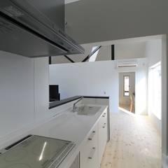 キッチンから家事室を見る: 石川淳建築設計事務所が手掛けたシステムキッチンです。