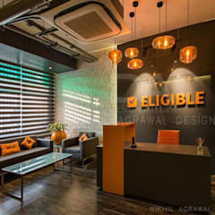 Reception with vibrant orange lights & exposed cassette A.C.:  Offices & stores by Design Atelier