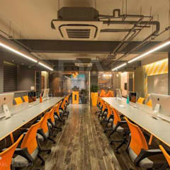 Workstation with an exposed ceiling & common seating arrangement for team members :  Offices & stores by Design Atelier