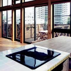 公園緑地に面した中庭のある自然素材住宅:ウッドデッキと連なる天井の高いリビング: 中浦建築事務所が手掛けたキッチン収納です。