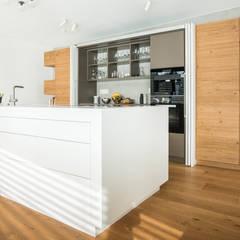 Einbauküche mit Kücheninsel:  Einbauküche von Mannsperger Möbel + Raumdesign