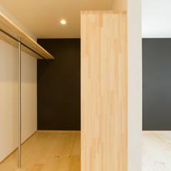 明るいリビングと大きな吹抜けのある家: KAWAZOE-ARCHITECTSが手掛けたウォークインクローゼットです。