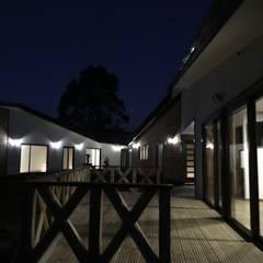Vista Nocturna Fachada Nor Poniente: Casas de madera de estilo  por Nomade Arquitectura y Construcción spa
