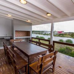 Terraza con parrilla y vista a la laguna: Terrazas de estilo  por JOM HOUSES
