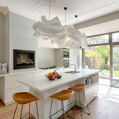 maatwerk keuken met openhaard en royale schuifpui naar de tuin:  Keukenblokken door StrandNL architectuur en interieur