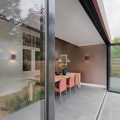 eetkamer met grote schuifpui in verbinding met tuin:  Eetkamer door StrandNL architectuur en interieur