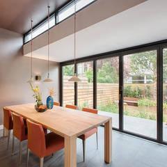 eetkamer met uitzicht op tuin dmv moderne schuifpui:  Eetkamer door StrandNL architectuur en interieur