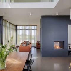 eetkamer met maatwerk openhaard en keuken:  Eetkamer door StrandNL architectuur en interieur