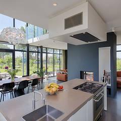keuken met uitzicht op maatwerk openhaard, eetkamer en omliggende tuin/landschap:  Keukenblokken door StrandNL architectuur en interieur
