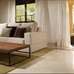 Salón con sofá en forma de L blanco y mesa de madera y hierro forjado sobre alfombra verde: Comedores de estilo  de AVANTUM