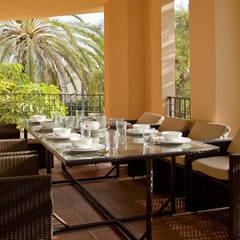 Terraza decorada con un juego de mesa y sillas de mimbre: Comedores de estilo  de AVANTUM