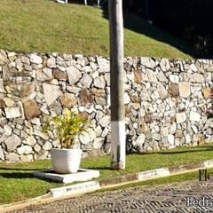 muros de arrimo de pedra bruta: Paredes  por Flora Flor do Campo Pedras e Paisagismo