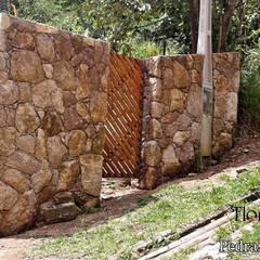 Muro de pedra na entrada da residencia : Paredes  por Flora Flor do Campo Pedras e Paisagismo