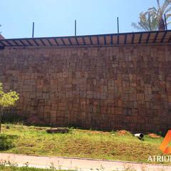 Muro de arrimo de pedra: Paredes  por Atrium Vale Pedras e Projetos