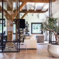 Verbouwing landelijke villa met moderne accenten: moderne Woonkamer door Bob Romijnders Architectuur & Interieur
