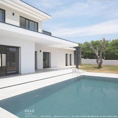 Vistas da casa sobre a piscina: Casas  por OGGOstudioarchitects, unipessoal lda