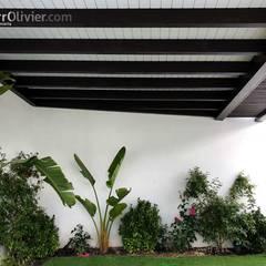Cubierta suspendida entre muros: Jardines de invierno de estilo  de NavarrOlivier