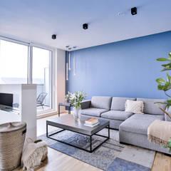 Salón con pared color turquesa: Salones de estilo  de Isabel Gomez Interiors