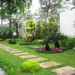 Jardines en la fachada de estilo  por Tukang Taman Surabaya - Tianggadha-art
