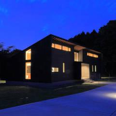 建物外観(南東からの夜景): TAPO 富岡建築計画事務所が手掛けた別荘です。