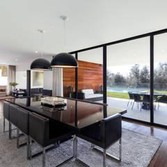 Sala de jantar com ligação ao patio e jardim exterior: Salas de jantar modernas por João Boullosa