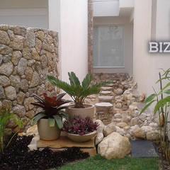 Muro em jardim de residencia com paisagismo: Paredes  por Bizzarri Pedras