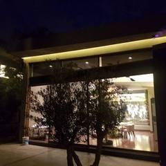 Iluminacion: Jardines en la fachada de estilo  por Ataxia Servicios