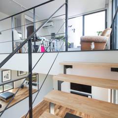 HU 厂型の屋根の家: 塚野建築設計事務所が手掛けたリビングです。