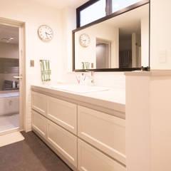 造作洗面台の大きなミラー: 塚野建築設計事務所が手掛けた浴室です。