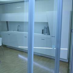 Design-Business-Kitchen mit in die Front integrierter LED-Leuchtleiste und schräg gestellten Korpussen.:  Geschäftsräume & Stores von RGenau Industries KG