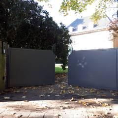 Jardines en la fachada de estilo  por Schmiedekunstwerk GmbH