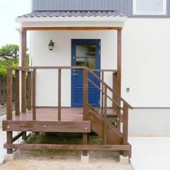 漆喰壁にはえる青い玄関ドア: デンマークハウスが手掛けた廊下 & 玄関です。