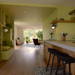 Sfeervolle lichte moderne woonkeuken met kookeiland en zwarte krukken:  Woonkamer door Denk Ruim Over Interieur