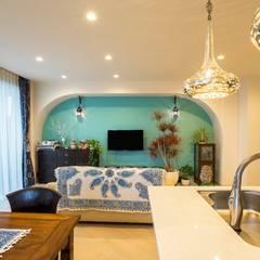 馬蹄形アーチとランプで彩られた魅惑的なモロッカンブルーの住まい: QUALIAが手掛けたリビングです。