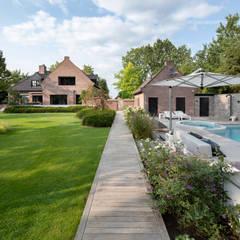 Zwembad met jacuzzi in de tuin:  Tuin door Studio REDD exclusieve tuinen