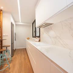 Cocina blanca con revestimiento imitación a mármol: Módulos de cocina de estilo  de Sincro