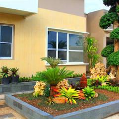 Jardines en la fachada de estilo  por Tukang Taman Surabaya - flamboyanasri,