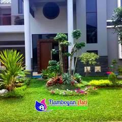 Jardines en la fachada de estilo  por Tukang Taman Surabaya - flamboyanasri