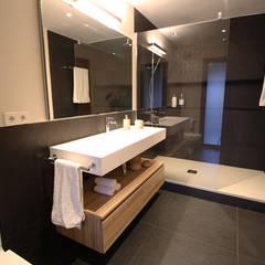La elegancia de un baño lleno de contrastes: Baños de estilo  de Obra de Eva