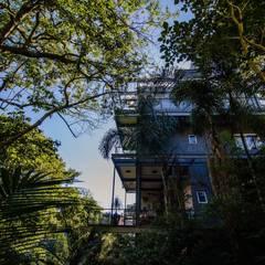 Residência em vidro suspensa na mata: Casas do campo e fazendas  por Karina Pontes Arquitetura