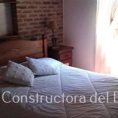Casa Costa del Este/Dormitorio 1 Dormitorios rústicos de Constructora del Este Rústico Ladrillos