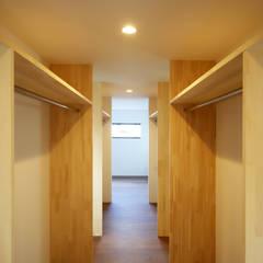 玄関の軒の存在感が異彩を放つ家: kisetsuが手掛けたウォークインクローゼットです。,モダン