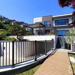 도심과 숲이 어우러진 주택단지에 위치한 고급주택 : 더존하우징의  전원 주택