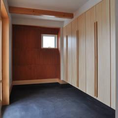室内と庭空間 敷地を一体化する三角形プラン: (株)独楽蔵 KOMAGURAが手掛けた廊下 & 玄関です。,