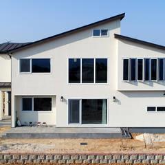 바다위 환하게 빛나고 있는 하얀집 : 더존하우징의  전원 주택