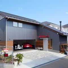 車3台収容!電動オーバーヘッドシャッターを採用した高品質木造ガレージハウス: (株)バウハウスが手掛けたガレージです。